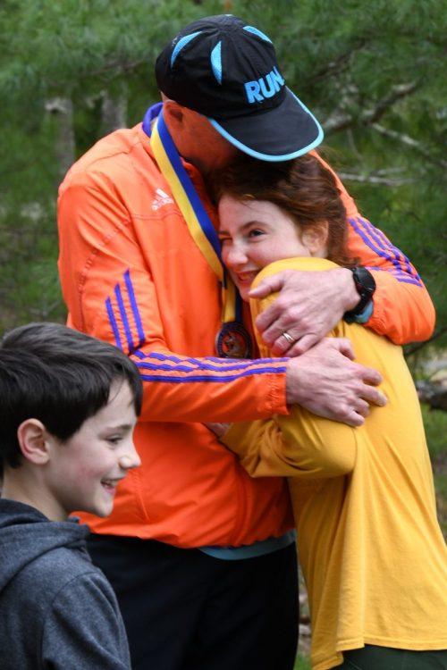 Matt Auger gets a hug from his daughter McKay after running 26.2 miles.