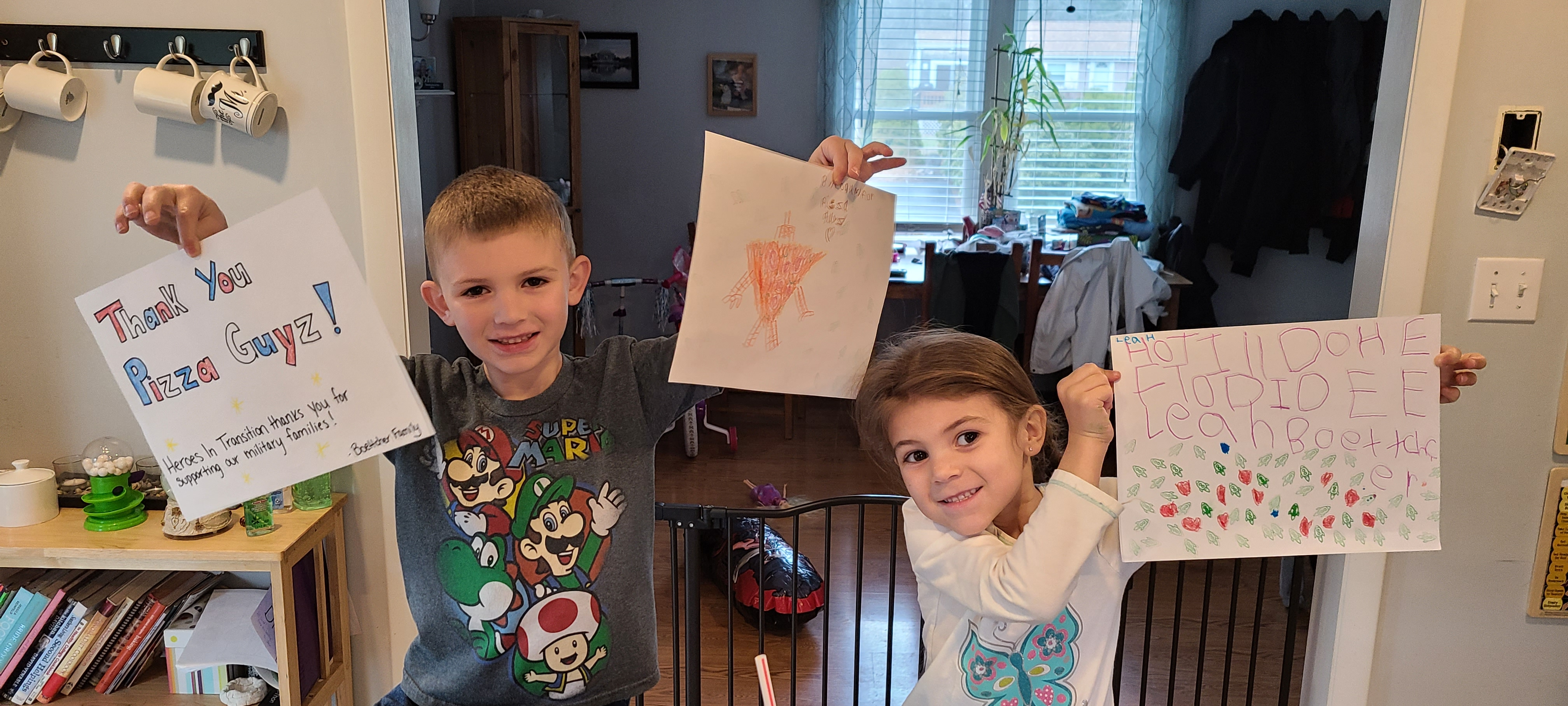 Children holding up thank you cards they made for the free pizza their families received from Heroes In Transition.