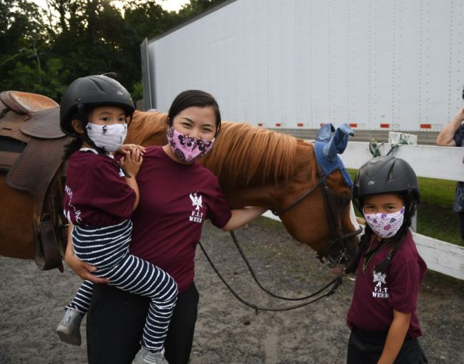 Rose Perez and her two daughters pose with their horse at Families In Transition (FIT) Week